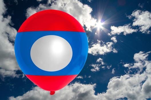 balloon in colors of laos flag flying on blue sky