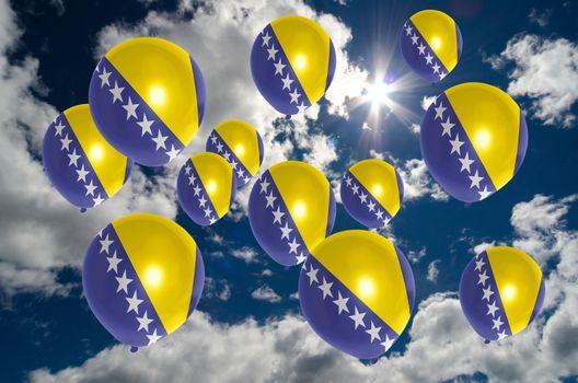 many ballons in colors of bosnia herzegovina flag flying on sky