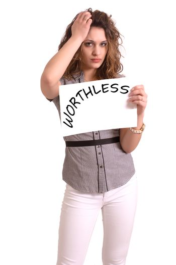 Young attractive woman holding paper with Worthless text on white background