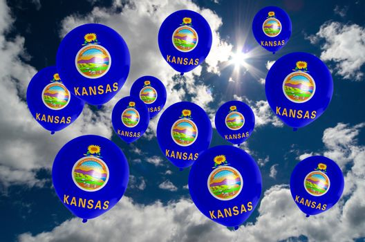 many ballons in colors of kansas flag flying on sky