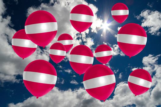 many ballons in colors of latvia flag flying on sky