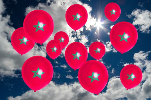 many ballons in colors of morocco flag flying on sky