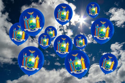 many ballons in colors of new york flag flying on sky