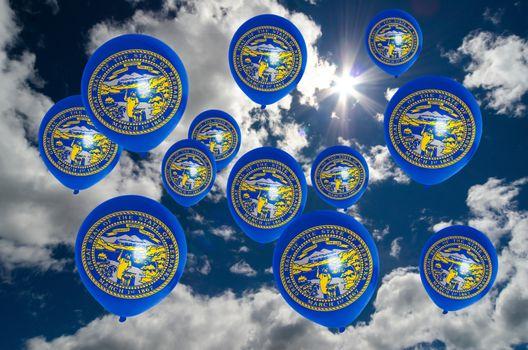 many ballons in colors of nebraska flag flying on sky