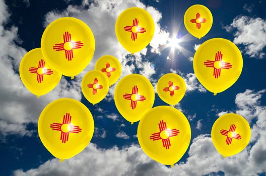 many ballons in colors of new mexico flag flying on sky