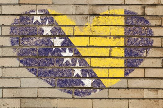 heart shaped flag in colors of bosnia herzegovina on brick wall
