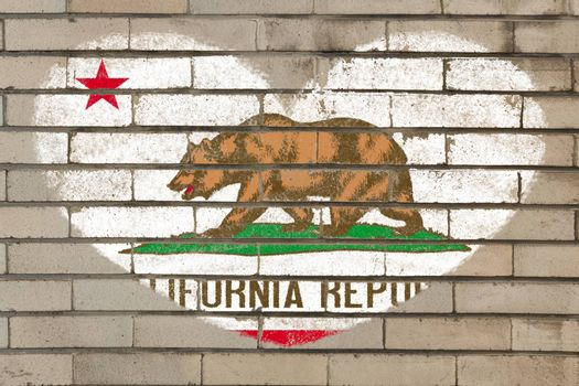 heart shaped flag in colors of california on brick wall