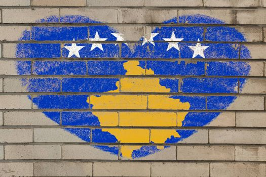 heart shaped flag in colors of kosovo on brick wall