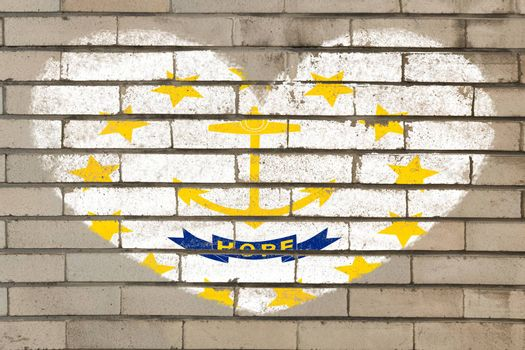 heart shaped flag in colors of rhode island on brick wall