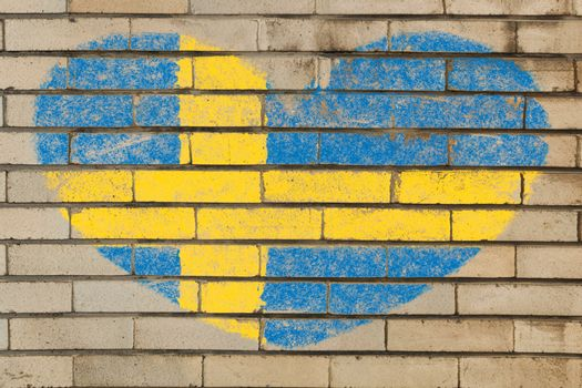 heart shaped flag in colors of Sweden on brick wall
