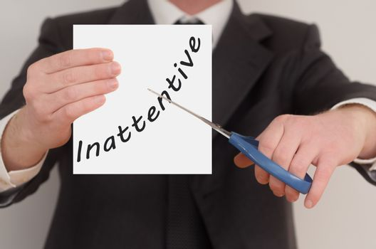 Inattentive, man in suit cutting text on paper with scissors