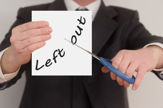 Left out, man in suit cutting text on paper with scissors