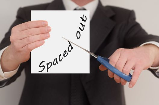 Spaced out, man in suit cutting text on paper with scissors