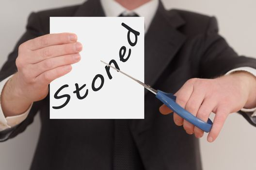 Stoned, man in suit cutting text on paper with scissors