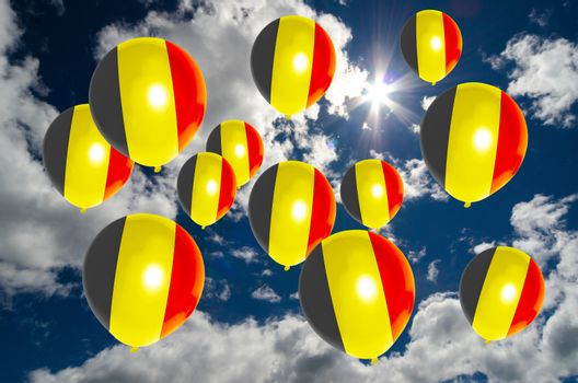 many ballons in colors of belgium flag flying on sky