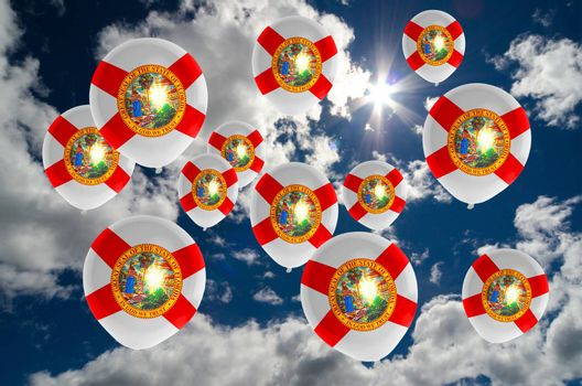 many ballons in colors of florida flag flying on sky