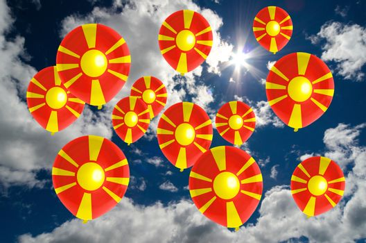 many ballons in colors of macedonia flag flying on sky
