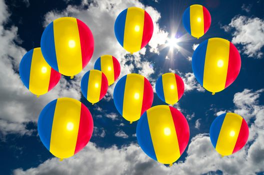 many ballons in colors of romania flag flying on sky