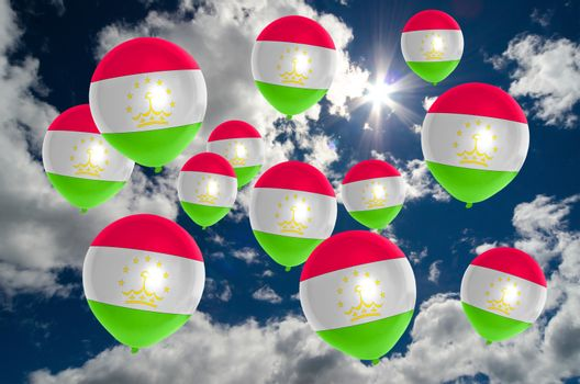 many ballons in colors of tajikistan flag flying on sky