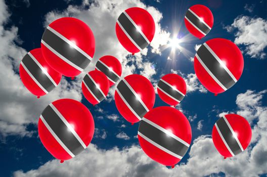 many ballons in colors of trinidad tobago flag flying on sky