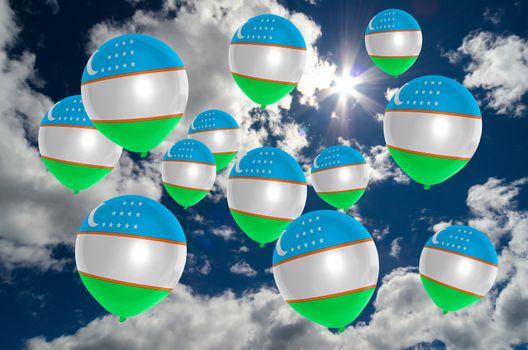 many ballons in colors of uzbekistan flag flying on sky