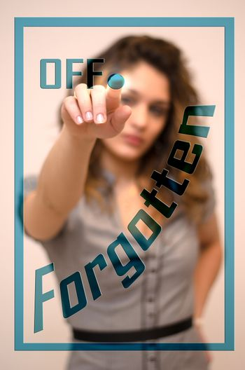 young woman turning offForgotten on hologram screen