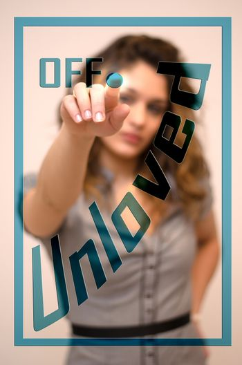 young woman turning offUnloved on hologram screen