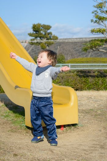 A 2 year old boy celebrating after going down a slide.