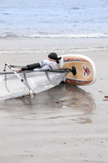 windsurfer having a nap on the beach in the maharees county kerry ireland