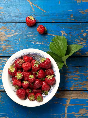 Fresh and ripe strawberries plate on the blue table