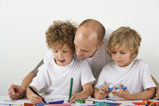 Father teaches his sons how to draw.