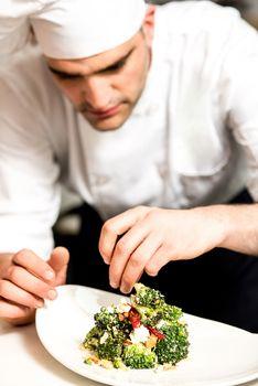 Cook decorating a broccoli salad