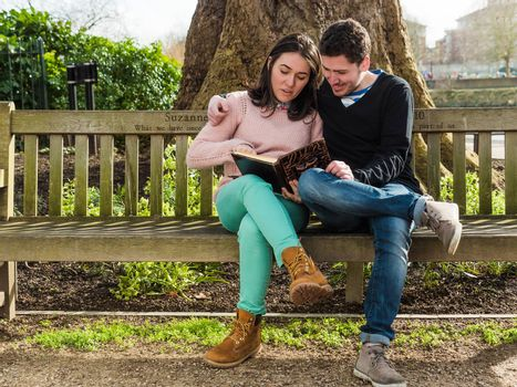 Young Couple Sitting on a Bench Reading a Book