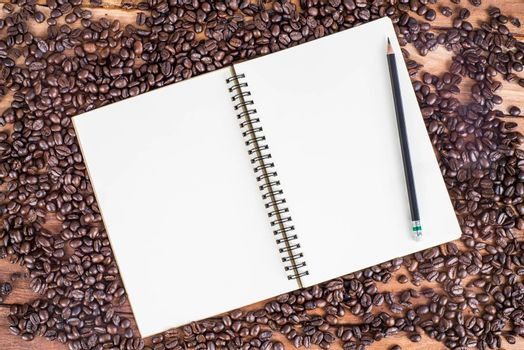 Pencil, notebook, coffee bean on wooden background