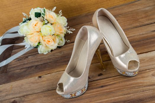 Wedding bouquet with bride's shoes on wood background
