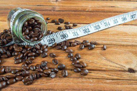 Coffee bean in glass bottle with tape measure on wooden backgrou