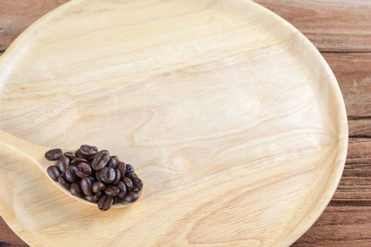 Coffee bean on wooden spoon, dish, table background