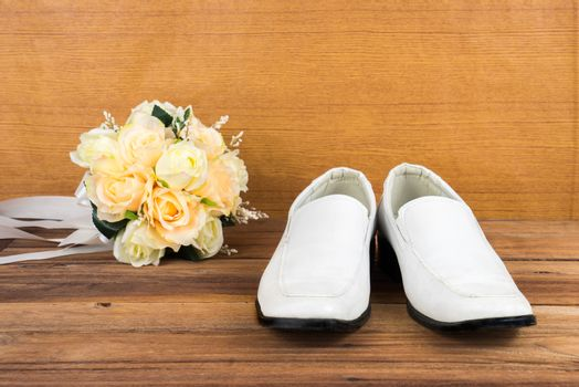 Wedding bouquet with groom's shoes on wood background