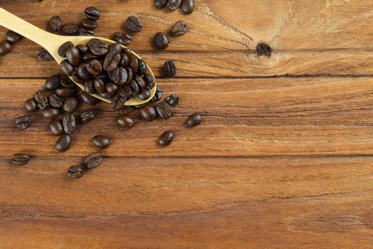 Coffee bean on wooden spoon, wooden table background