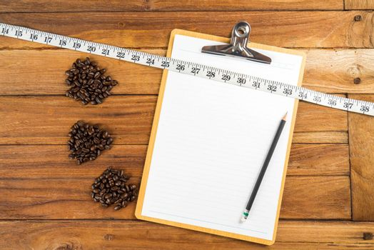 Wooden Clipboard attach planning paper with pencil beside coffee