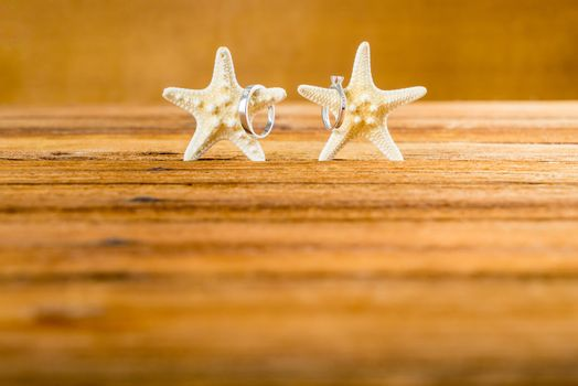 Two wedding rings with two starfish on wooden table