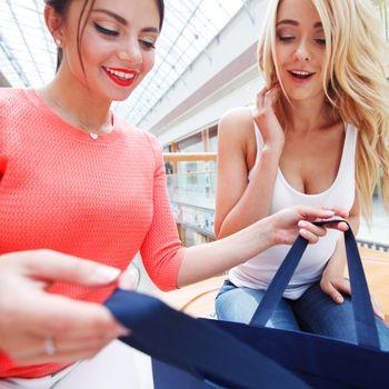 Young beautiful happy women looking into shopping bag