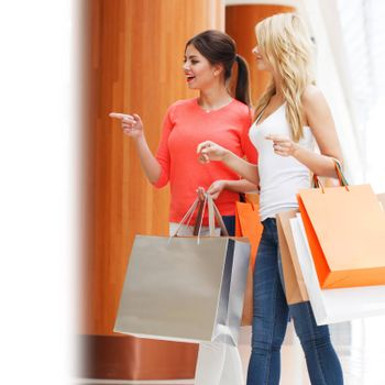 Young beautiful happy women with shopping bags in mall