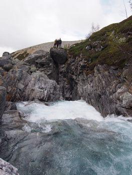 People standing on rock over waterfall in Skjåk, Norway