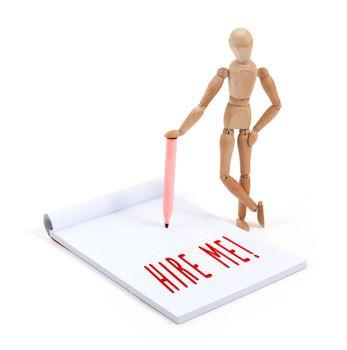 Wooden mannequin writing in scrapbook - Hire me