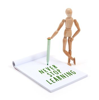 Wooden mannequin writing in scrapbook - Never stop learning
