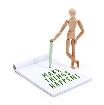 Wooden mannequin writing in scrapbook - Make things happen
