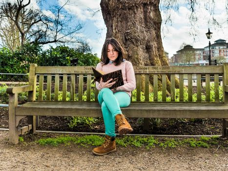 A Casual Young Woman Sitting on a Bench in a Park and Reading Her Book