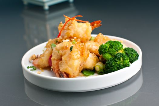 Thai style crispy honey shrimp dish presented beautifully on a round white plate with copy space above.