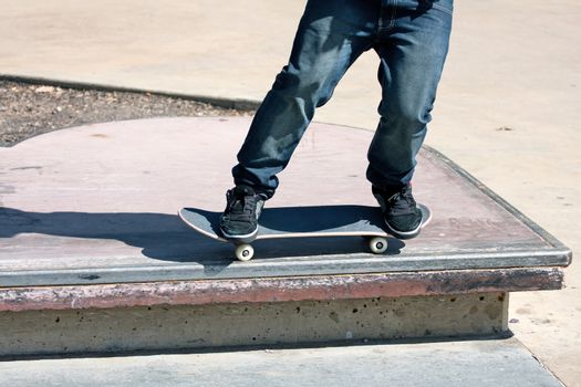 Close up of a skateboarders feet while skating across a rail at the skate park.  Shallow depth of field.